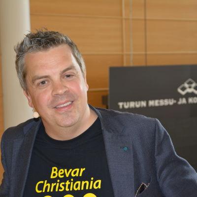 Professor Alf Rehn på Åbo mässcentrum, i t-skjorta med texten: Bevar Christiania.