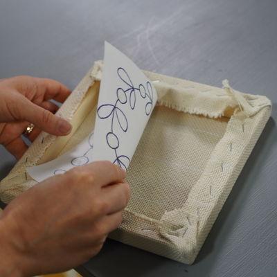 Händer sätter mönsterpapper inne i tuftningsramen