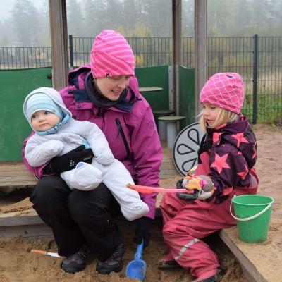 Äiti ja kaksi lasta istuvat hiekkalaatikon reunalla.
