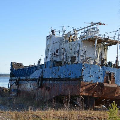 En gammal och rostig båt står på land.