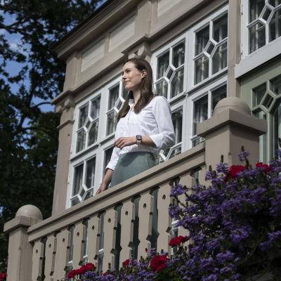 Sanna Marin på trappan till Villa Bjällbo, med snickarglädje i bakgrunden.