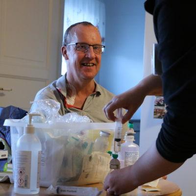 En man med glasögon sitter framför ett bord med läkarutrustning och medicin.