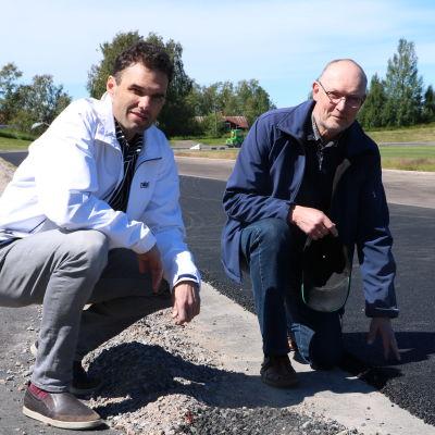 Två män sitter på huk intill en idrottsbana som renoveras.