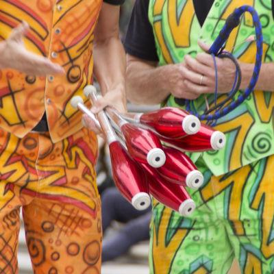 Två personer med väldigt färgglada kläder. Den ena personen håller i ett knippe röda jongleringskäglor.