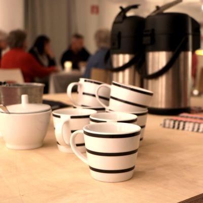 I förgrunden kaffekoppar, i bakgrunden deltagare i vänskapskaféet i Luckan i Helsingfors.