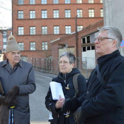 Tre människor, en kvinna och två män, står framför silorna i Vasa.