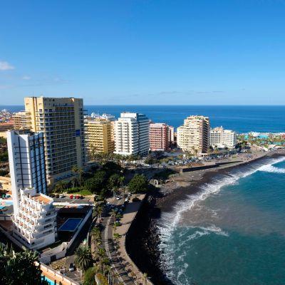 En strand kantad av höga hotell.