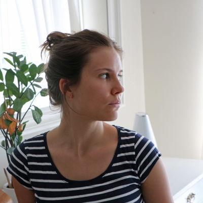 En kvinna står framför ett fönster och tittar förbi kameran till höger.