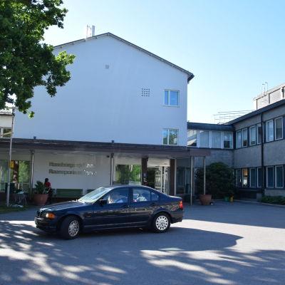 RAseborgs sjukhus, huvudingången fotograferad utifrån. En svart bil står perkerad utanför dörren. Sommar.