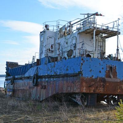 En rostig båt står vid en hamn på vintern.