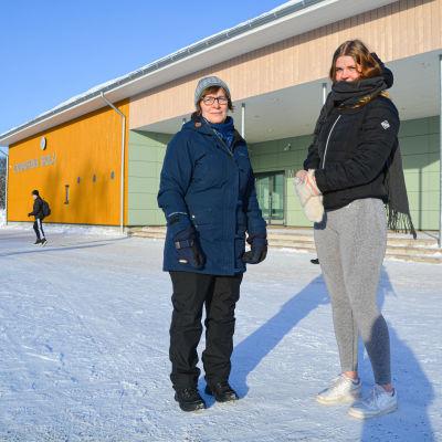 En kvinna och en flicka utanför en skola.