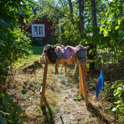 Fyra käpphästar som lutar på en ställning i en gång mellan två buskar.