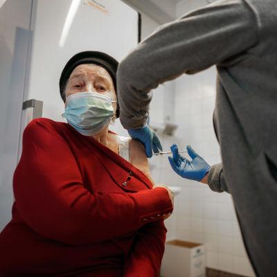 En äldre kvinna får coronavaccin.