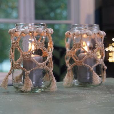 Två glasburkar gjorda till lyktor med ljus i och makramédekorationer utanpå.
