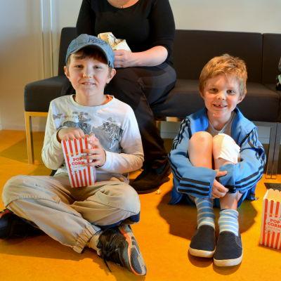 Två pojkar sitter på golvet framför en bänk och äter popcorn