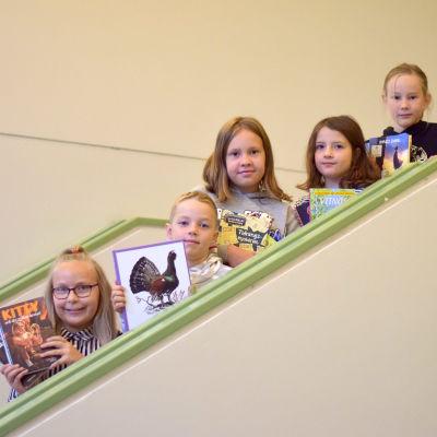 Fem barn i tioårsådern står i en trappa med böcker i händerna.