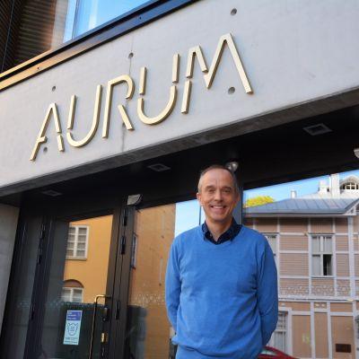 En man i blå tröja och mörkblå byxor står framför ingången till Aurum, Åbo Akademis nya byggnad.