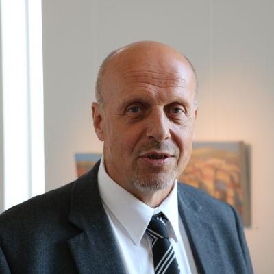 Göran Honga står i mörk kavaj i ett galleri i Närpes.