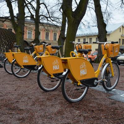 Flera granngula stadscyklar står på rad på stadscykelstation i Åbo.