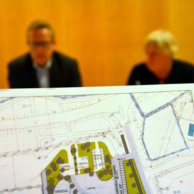 En karta över Pargas skolcentrum, med två personer i bkagrunden.