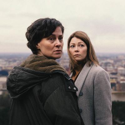 Rita (Lotta Lehtikari) ja Laura (Niina Koponen) katsovat olkansa yli huolestuneen näköisinä kaupunkimaisena taustallaan.