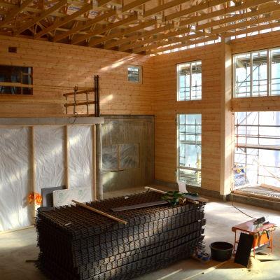 Ett stort och högt rum i trä, med stora fönster där ljuset strålar in