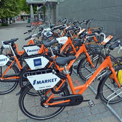Orangea cyklar i en cykelställning.