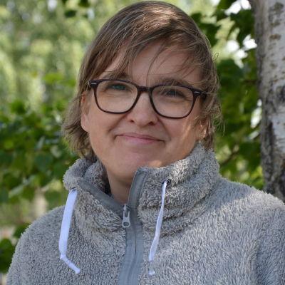 Kvinna i grå tröja ser in i kameran, i bakgrunden gröna björklöv.