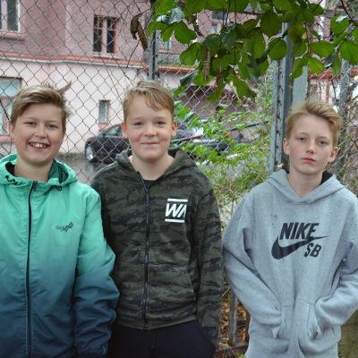 Tre lågstadiepojkar står vid ett stålstängsel på en skolgård.