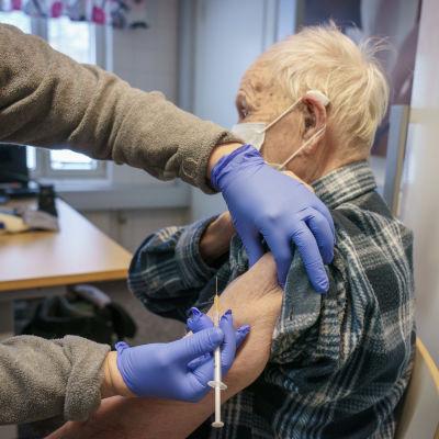 Sairaanhoitaja antamassa koronarokotetta.