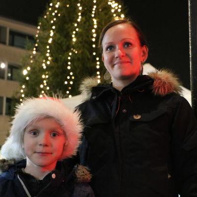 Barn med tomtemössa står med sin mor framför julgran som är upplyst.