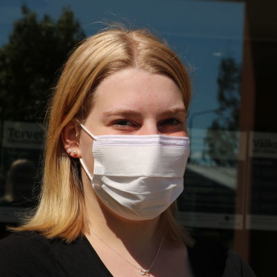 En kvinna med blont hår och munskydd för ansiktet står framför ett fönster.