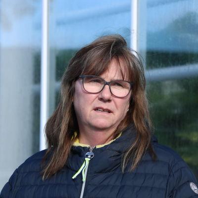 En kvinna med långt brunt hår och glasögon står intill ett växthus.