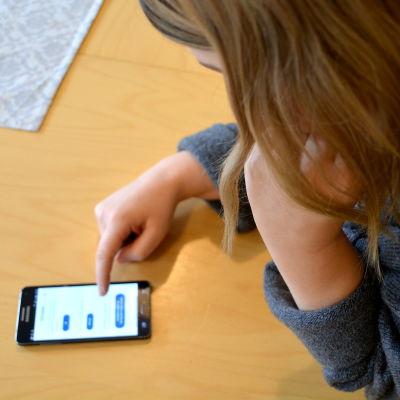 Nuori tyttö katsoo pöydällä olevaa matkapuhelinta.