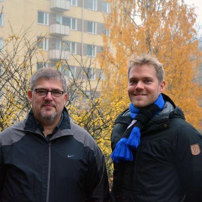 Två män står utomhus. Bakom dem ett hus samt börjar med gula höstlöv.