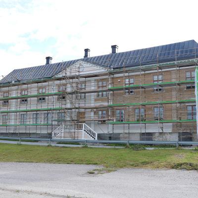 En husfasad som renoveras. Längs med hela fasaden har byggställningar lagts upp.