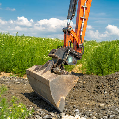 En grävskopa är i beråd att gräva i en fläck brun jord omringad av grön växtlighet på en höjd cirka en halv meter.