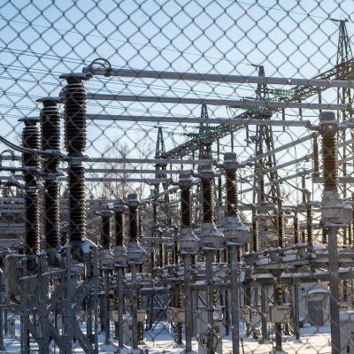 Sähköaseman laittteistoa verkkoaidan läpi kuvattuna.