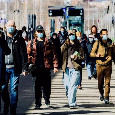 Människor med ansiktsmask vid Helsingfors jänrvägsstation.