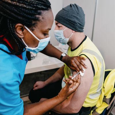 En sjukskötare ger ett coronavaccin till en man.