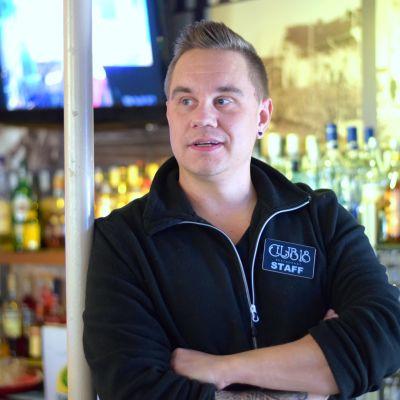 Man i svart tröja framför en hylla med flaskor. Har armarna i kors och tittar åt sidan.