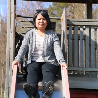 En asiatisk kvinna i 50-årsåldern sitter i en rutschkana.
