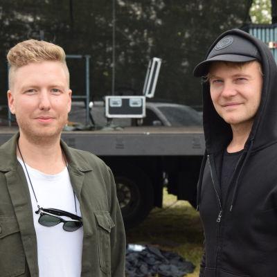 Två unga män står framför en konsertscen. Utomhus.