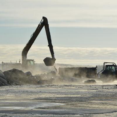en grävskopa lassar äver muddringsmassor i ett traktorsläp på isen.