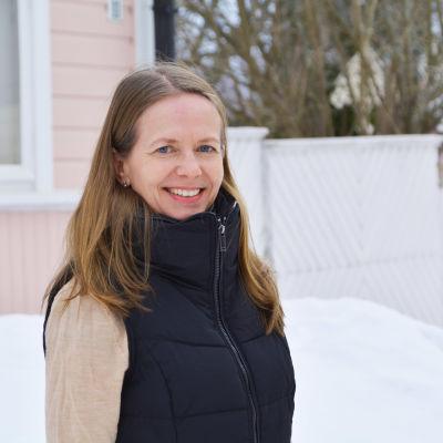 Leende kvinna (rektor Carina Stenbacka) framför ljusrött trähus.
