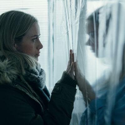 Nina Kautsalo (Iina Kuustonen) seisoo muovin toisella puolella ja hänen siskonsa (Pihla Viitala) toisella puolella kädet muovin läpi koskettaen.