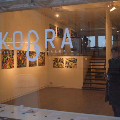 Kvinna står inne i ett konstgalleri.
