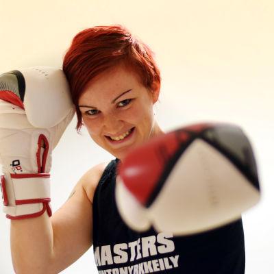 En bild på en kvinna (Emmy Erroll) med rött kort hår som boxar mot kameran med en boxningshandske.