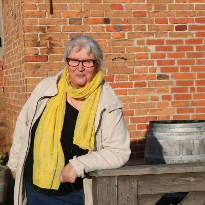 En kvinna i halsduk och glasögon framför en tegelvägg.