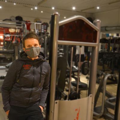 Kvinna i gym med olika träningsredskap.